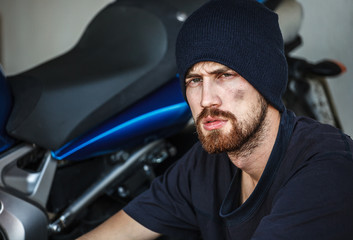 Portrait of Serious young man with his motorcycle on background