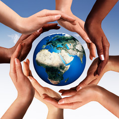 Multiracial hands making a circle together around the world glob