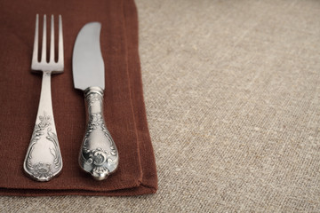 Vintage fork and knife on napkin with tablecloth and copyspace.