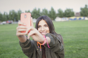 Beautiful young woman taking a selfie with phone