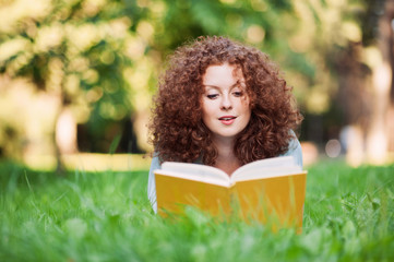 Beautiful girl reading a book in a summer green park