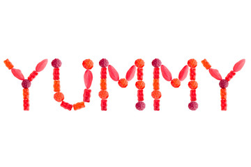"Word ""YUMMY"" made of red sugary candies, isolated"