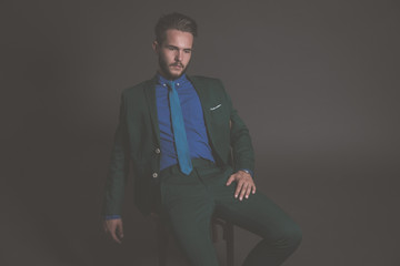 Business fashion man wearing green suit with blue shirt and tie.