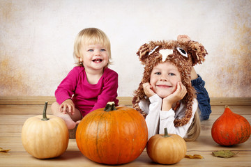 Two little sisters with pumpkins