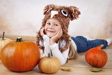 Funny little preschooler with pumpkins
