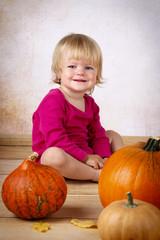 Little girl with pumpkins