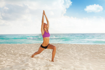 Woman with arms up and legs apart making yoga
