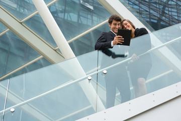 Young business couple with modern building behind  with tablet