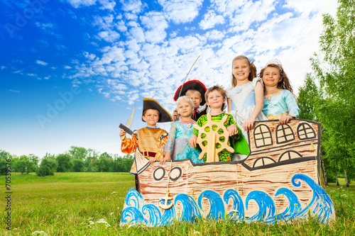 Happy children in costumes standing on ship - 70539576