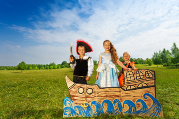 Pirate with sword and two princesses stand on ship