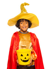 Boy in wizard costume with candy Halloween bucket