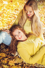 Two young girl in autumn forest