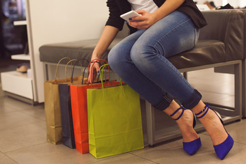 Girl with shopping bags, texting