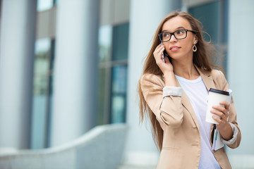 Successful businesswoman with cellphone while walking outdoor. C