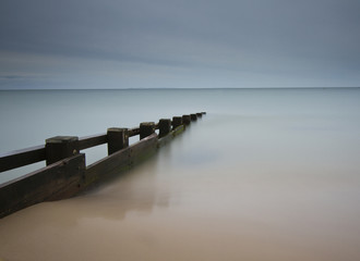 Seascape with smooth water and groyne