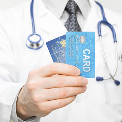 Male doctor holding two credit cards in his hand - 1 to 1 ratio