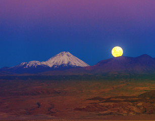 Full-moon in the Moon Valley. Volcanoes Licancabur and Juriques
