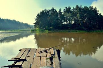 wooden bridge on the lake with a fishing rod