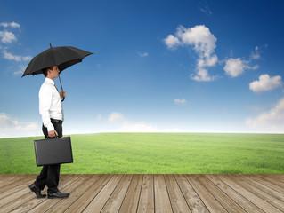 Mann mit Regenschirm in der Landschaft