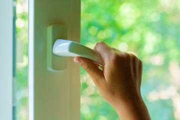 Сhild's hand opens a plastic window