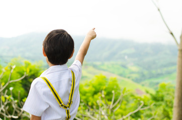 Little boy pointing his finger to the sky on the hill