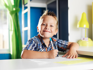 little boy doing homework in room with happy face