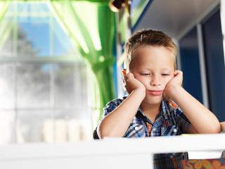 bored little boy tired of doing homework