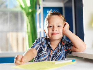 little boy with home work looking at camera