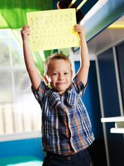 cute little boy showing his alphabet worksheet