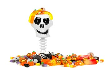 Halloween skull candy holder with pile of candy over white