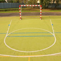 Empty outdoor handball playground, plastic light green surface