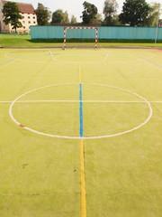 Empty outdoor handball playground, plastic light green surface