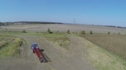 Flight behind  agricultural tractor in field. Aerial