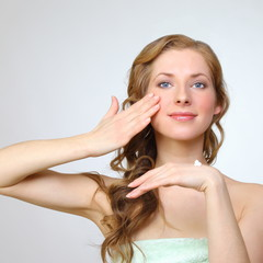 Beauty face of young woman with cosmetic cream