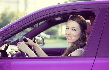 Happy smiling woman, buckled up, driving new car