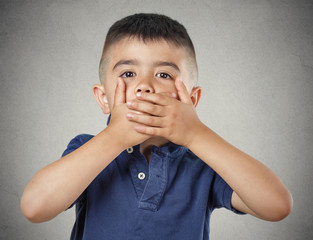 Boy closing, covering mouth with hands speak no evil concept