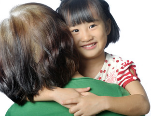 little asian granddaughter smiling in senior woman's arm
