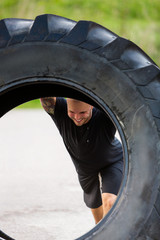 Athlete Lifting Large Tractor Tire On Street