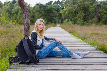 Blonde girl resting on wooden path in nature