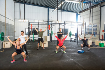 Trainers Assisting Athletes In Exercising With Barbells