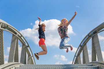 Two happy teenage girls jumping on bridge