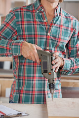 Midsection Of Male Carpenter Drilling Wood