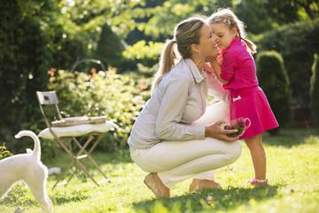 Mutter und Tochter im Garten kuscheln