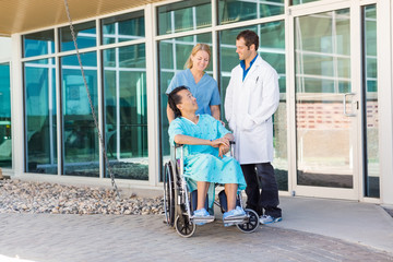 Nurse And Doctor Looking At Patient On Wheelchair Outside Hospit