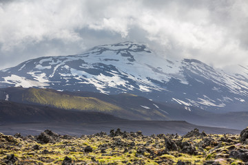 Icelandic volcano with snow and cloudy sky