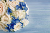 Beautiful wedding bouquet with roses on blue wooden table