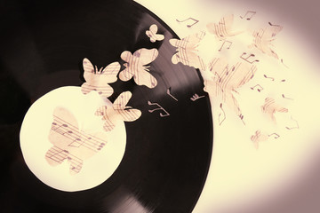 Old vinyl record with paper butterflies, close-up