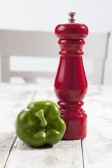 Grüne Paprika, rote Pfeffermühle auf weissem Holztisch