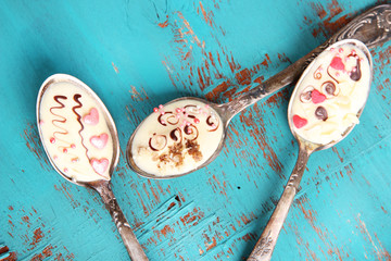 Spoons with tasty chocolate for party on old blue wooden table