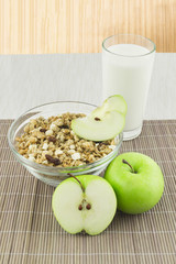 Cereal with milk and apple on the mat